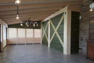 Rivestimento di parete con legno morderzato verde e sullo sfondo frangisole in legno di abete